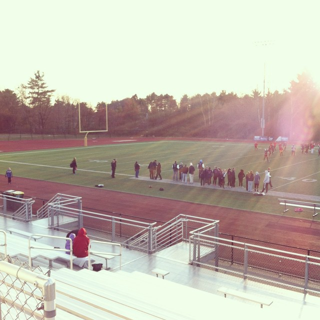 Empty bleachers at the Powderpuff game; people swarm the sidelines
